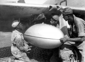 Members of the ground crew of the fighter squadron of the 15th U.S. Air Force in Italy place a loaded wing tank on a P-51 Mustang before the group takes off on another mission escorting bombers over enemy targets. The squadron uses the auxiliary fuel tanks for long distance flights. Left to right: T/Sgt. Charles K. Haynes, S/Sgt. James A. Sheppard, and M/Sgt. Frank Bradley