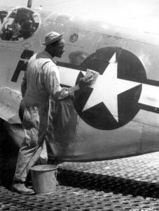 Staff Sgt. William Accoo..., crew chief in a Negro group of the 15th U.S. Air Force, washes down the P-51 Mustang fighter plane of his pilot with soap and water before waxing it to give it more speed.