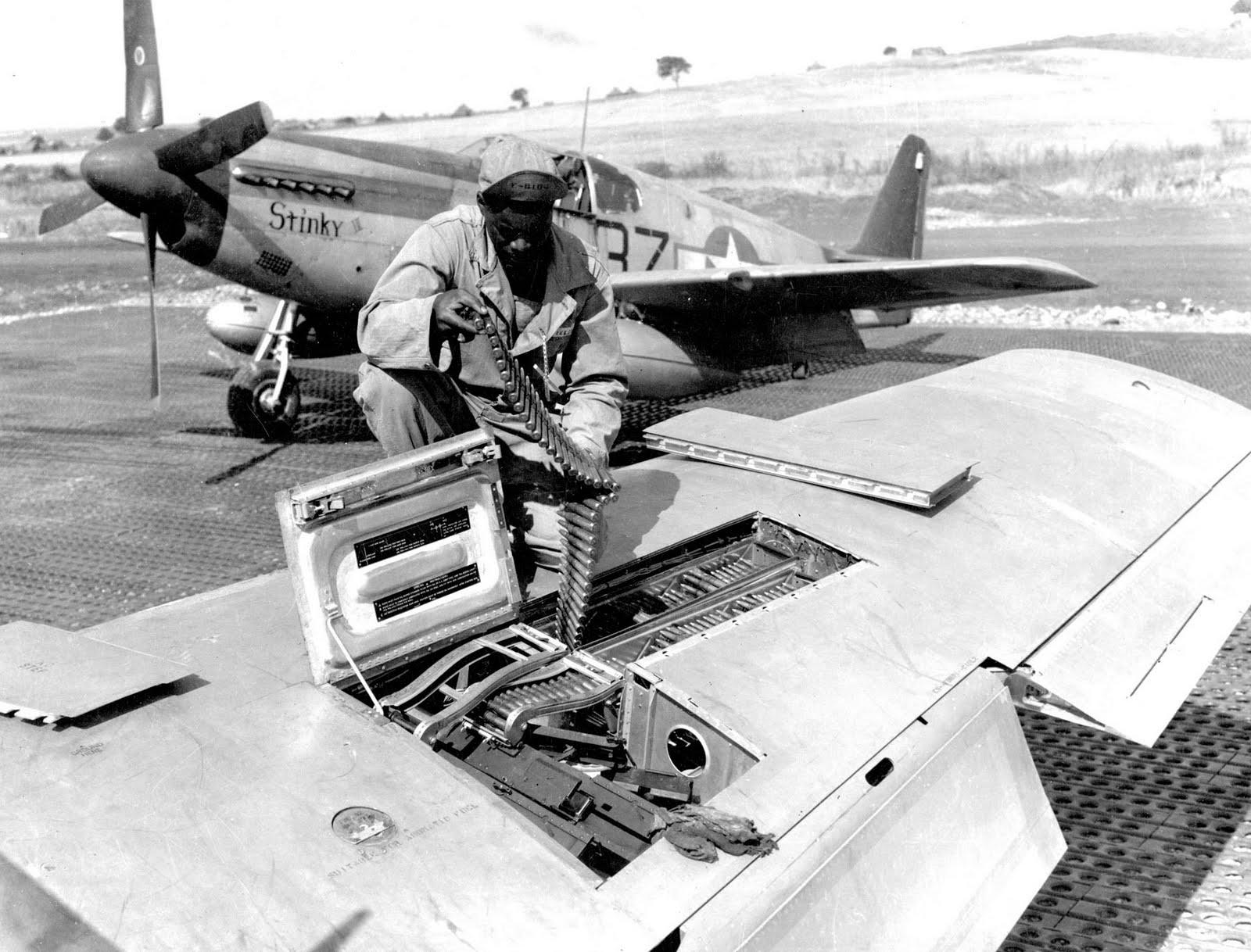 Support crew arming the aircraft's .50 caliber machine guns.