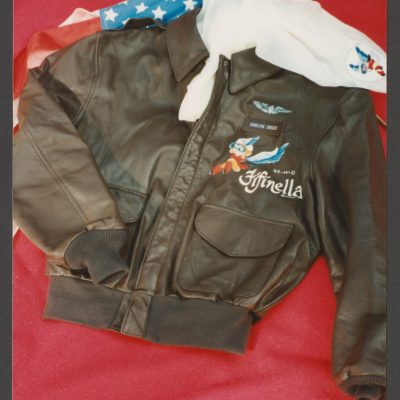 Charlyne Creger's brown bomber jacket with diamond wings and Fifinella emblems, and white scarf with an image of Fifinella with part of an American flag visible in the background.